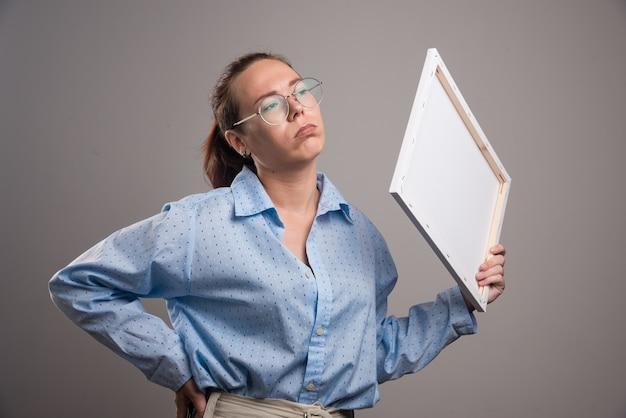 Femme à lunettes tenant toile et pinceau sur fond gris. photo de haute qualité