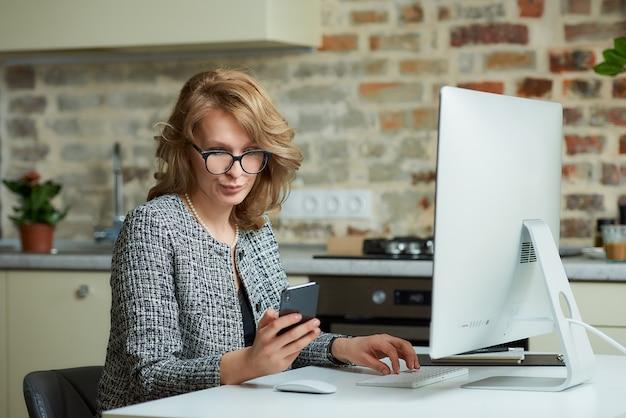 Une femme à lunettes travaille à distance sur un ordinateur de bureau dans son studio. un patron distrait par un smartphone lors d'une visioconférence à domicile.