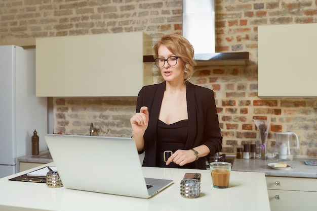 Une femme à lunettes travaille à distance sur un ordinateur portable dans sa cuisine. une fille blonde avec des accolades gesticulant discute avec ses collègues lors d'une vidéoconférence à la maison.