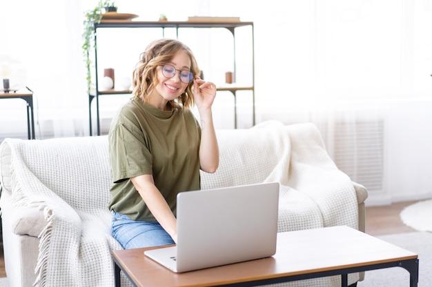 Une femme avec des lunettes utilise un clavier de saisie pour ordinateur portable assis sur un canapé grande fenêtre arrière-plan intérieur de la maison femme indépendante travaillant à domicile étudiant à distance relaxant regarder des leçons vidéo conférence