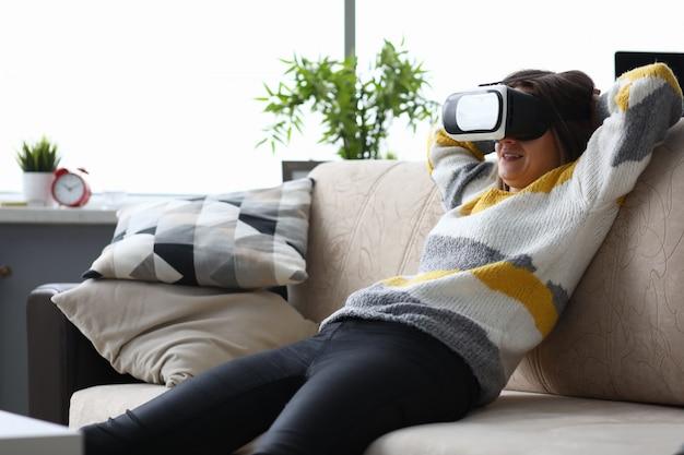 Femme à lunettes virtuelles assis sur le canapé