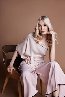Femme de luxe en robe assise sur une chaise