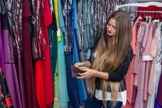 Femme en magasin de vêtements posant avec portefeuille