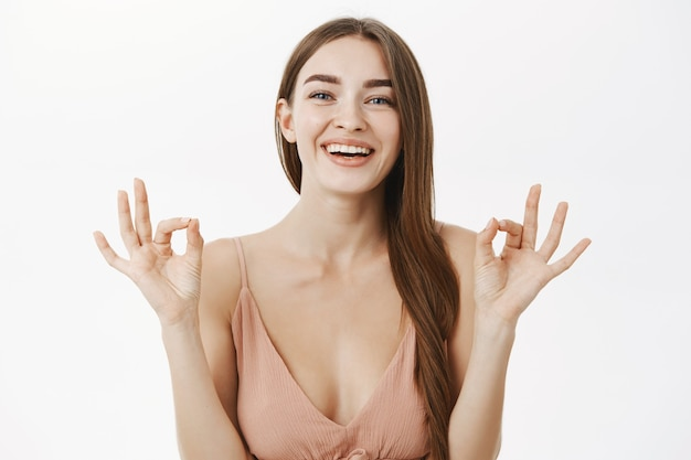 Femme magnifique européenne heureuse optimiste en robe beige à la mode montrant un geste correct ou parfait