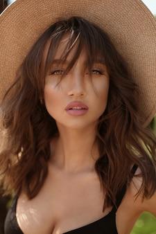 Une femme magnifique, avec des lèvres charnues sensuelles et un maquillage parfait, dans un maillot de bain noir et un chapeau posant dans la piscine en plein air un jour d'été.