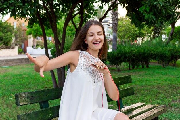 Une femme magnifique mignonne écoute de la musique avec des écouteurs et danse sur un banc dans le parc dans une journée chaude