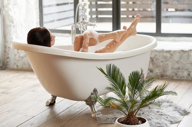 Une femme magnifique s'amuse dans une baignoire blanche, dans une pièce lumineuse avec une grande fenêtre.