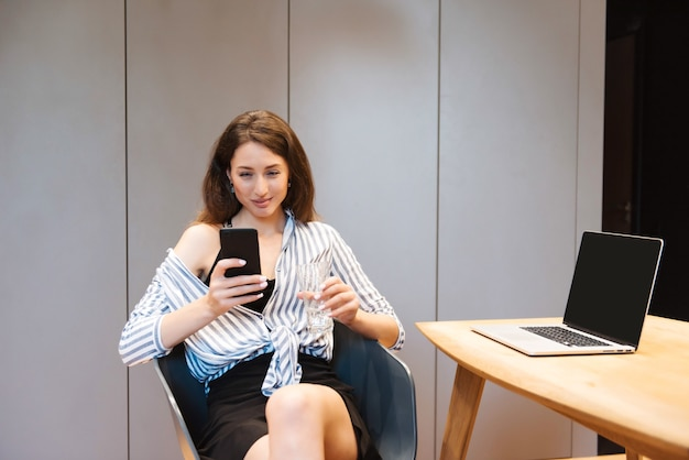Femme magnifique souriante aux cheveux bruns, assise confortablement sur une chaise et utilisant un smartphone personnel
