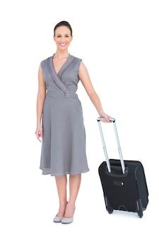 Femme magnifique souriante portant sa valise