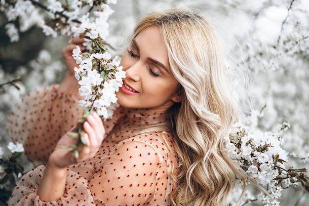 Femme avec un magnifique sourire, des cheveux blonds bouclés en robe rouge s'amusant dans un jardin fleuri