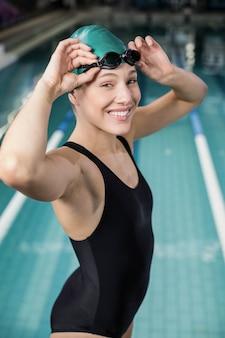 Femme en maillot de bain ajustant ses lunettes à la piscine