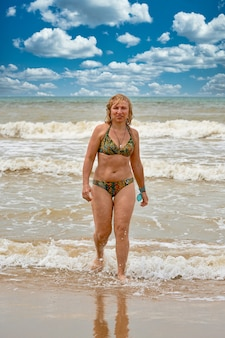 Une femme en maillot de bain aux cheveux longs blancs sort de la mer