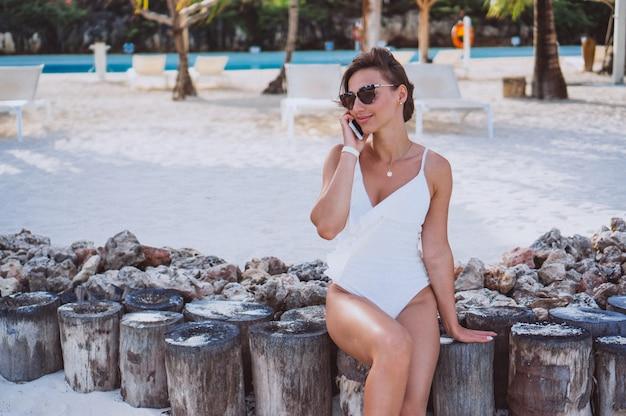 Femme en maillot de bain blanc au bord de l'océan à l'aide d'un téléphone