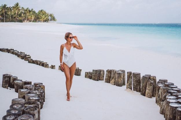 Femme en maillot de bain blanc au bord de l'océan