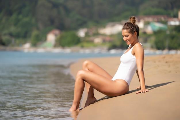 Femme en maillot de bain blanc bronzer sur la plage