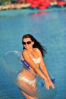 Une femme en maillot de bain blanc avec un cercle gonflable dans un parc aquatique