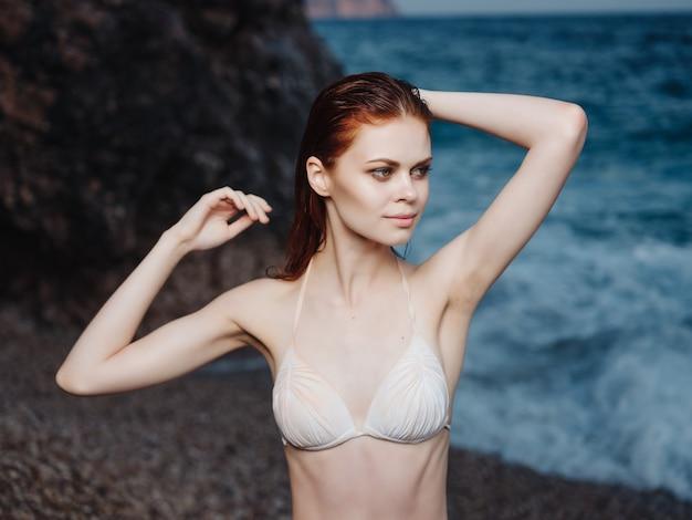 Femme en maillot de bain blanc près de la mode loisirs de luxe de l'océan