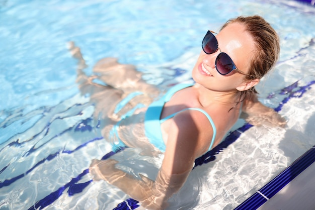 Femme en maillot de bain bleu s'asseoir dans la piscine.
