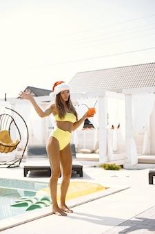 Femme en maillot de bain et chapeau de noël tenant un verre et buvant un cocktail près de la piscine.