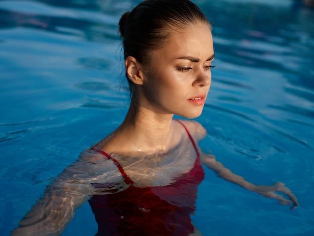 Femme en maillot de bain dans la piscine avec les yeux fermés de luxe