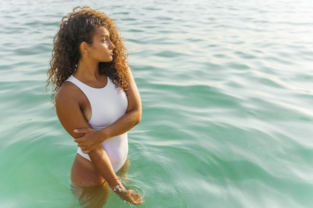 Femme en maillot de bain debout dans la mer en regardant l'horizon