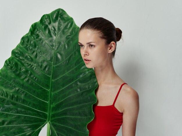 Femme en maillot de bain feuille de palmier vue de côté fond isolé