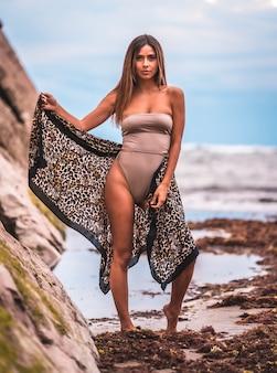 Femme en maillot de bain marron et sarong sur un fond naturel à côté de rochers et de la mer