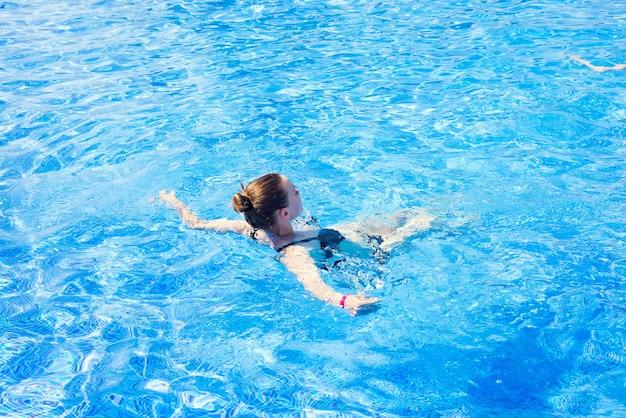 Femme avec maillot de bain nageant dans une piscine d'eau bleue, concept de vacances de vacances tropicales