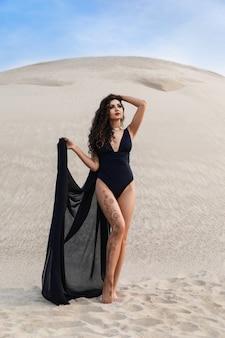 Femme en maillot de bain noir et avec mehendi sur la plage