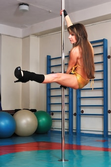 Femme en maillot de bain or et chaussures noires est un élément de danse d'entraînement sur un poteau. salle de sport et de danse