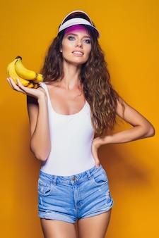Femme, maillot de bain, et, short bleu, tenue, banane, et, poser, isolé, sur, scène jaune