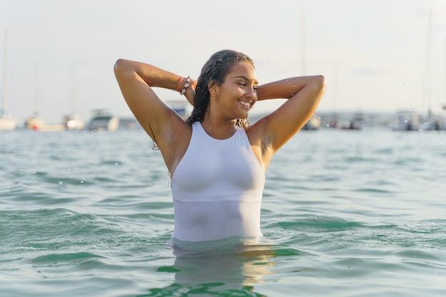 Femme en maillot de bain souriant dans la mer