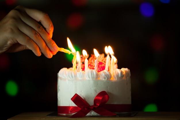Femme main allumer la bougie sur le gâteau d'anniversaire dans le ton foncé