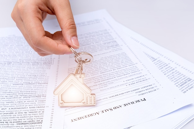 Femme main et clé de la maison.
