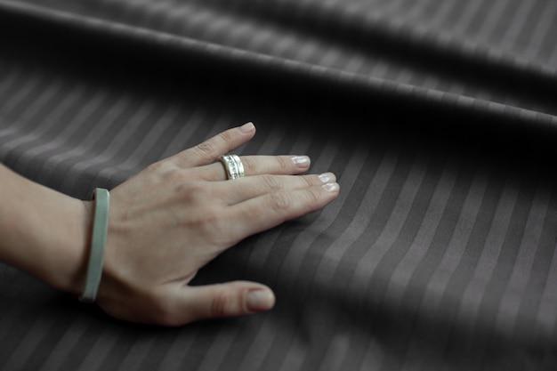 Femme main contre un tissu marron plié