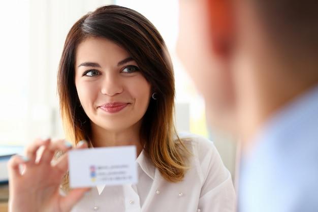 Femme main en costume donner carte de visite vierge au visiteur