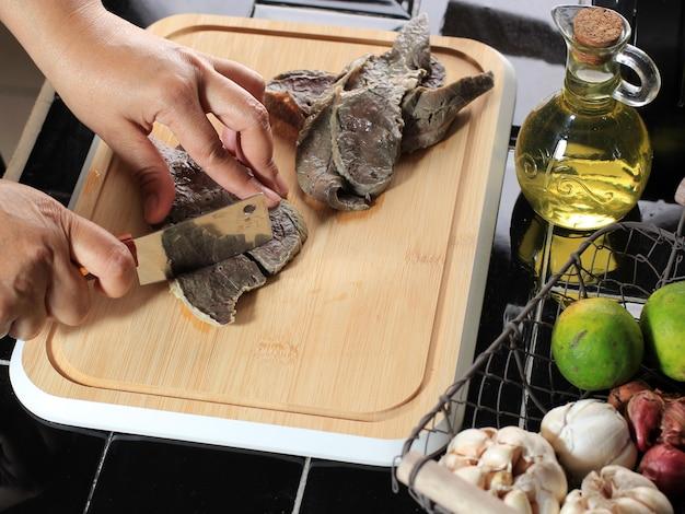 Femme main coupé les poumons de boeuf bouilli (paru) avec un couteau sur une planche à découper en bois dans la cuisine. processus de cuisson faire des aliments faits maison à partir de poumons de boeuf