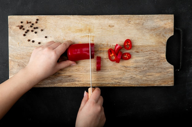 Femme main couper le poivre sur une planche à découper avec des épices de poivre sur le tableau noir