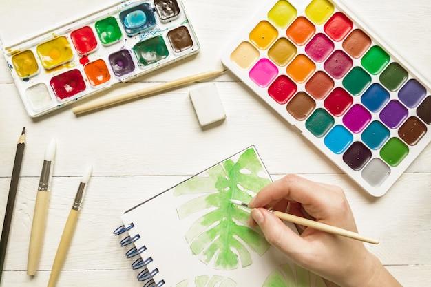 Femme main croquis peinture aquarelle de feuille de monstera. peintures et pinceaux aquarelles, vue de dessus. mise à plat artistique créative.