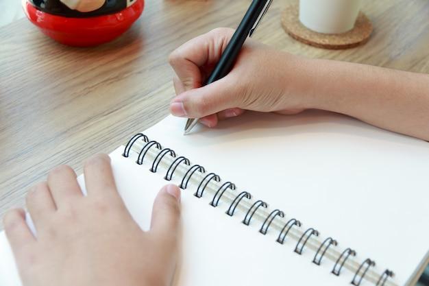Femme main écrivant sur papier avec un stylo sur un bureau en bois au café