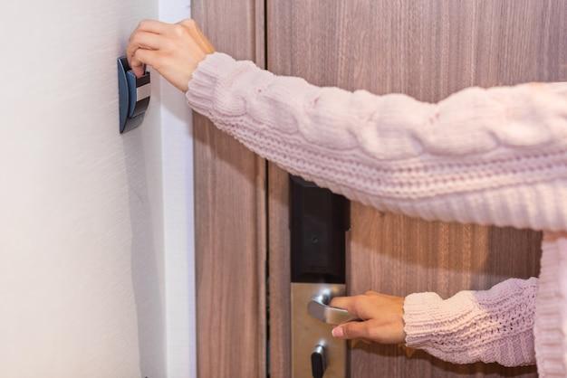 Femme main insérant une carte dans la chambre d'hôtel