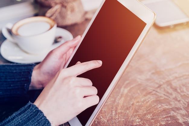 Femme main jouant la tablette dans un café avec ton vintage.