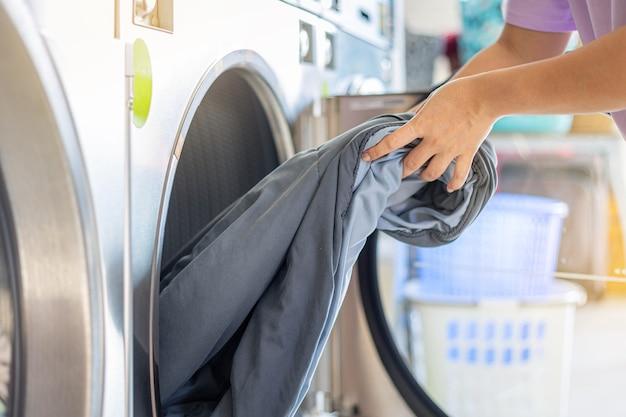 Femme de main lavant dans une laverie automatique. laveuse et sécheuse de pièces avec système de paiement intégré.