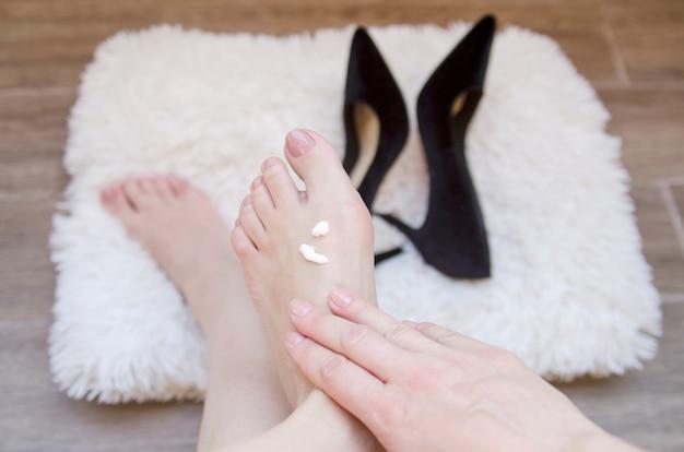 Femme main massage du poignet pieds nus après la marche en talons hauts.