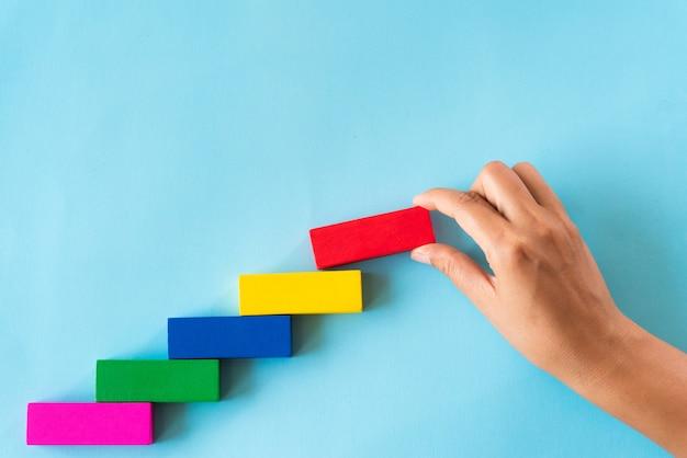 Femme main mettre un bloc de bois rouge sur des blocs de bois colorés en forme d'escalier