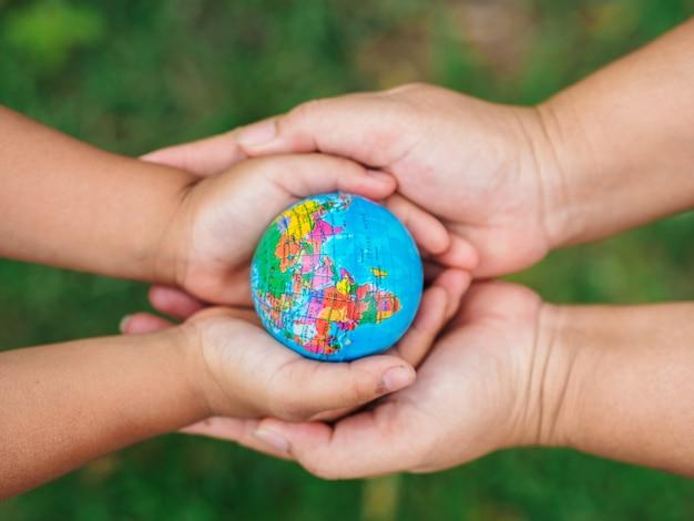 Femme main et petit giel haand tenant le globe