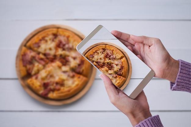 Femme de main avec pizza photographie pull avec smartphone. concept de restauration rapide et de technologie.