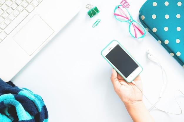 Femme à la main plate main tenant téléphone portable et ordinateur portable blanc avec des papeterie de couleur verte et collage d'accessoires pour fille sur fond blanc. concept de couleur verte