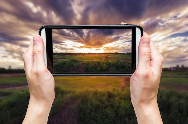 Femme de main prenant la photo au coucher du soleil.