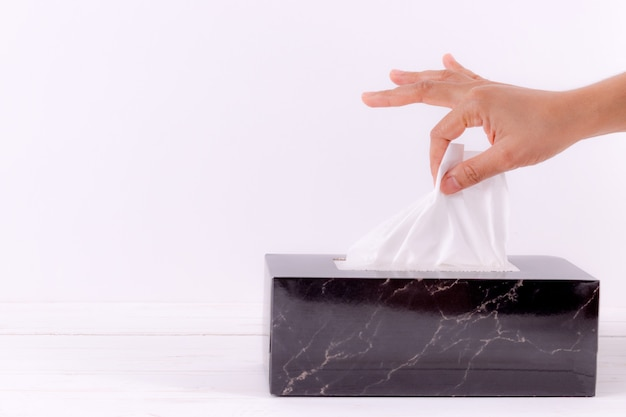 Femme main ramassant du papier de soie blanc dans une boîte de mouchoirs.